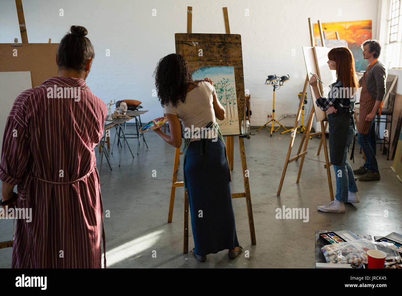 Adult students painting on artists canvas in art class - Stock Image