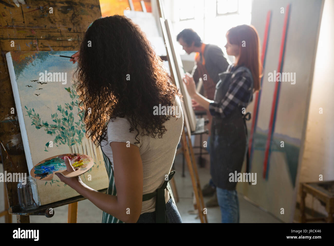Adult friends painting on artists canvas in art class - Stock Image