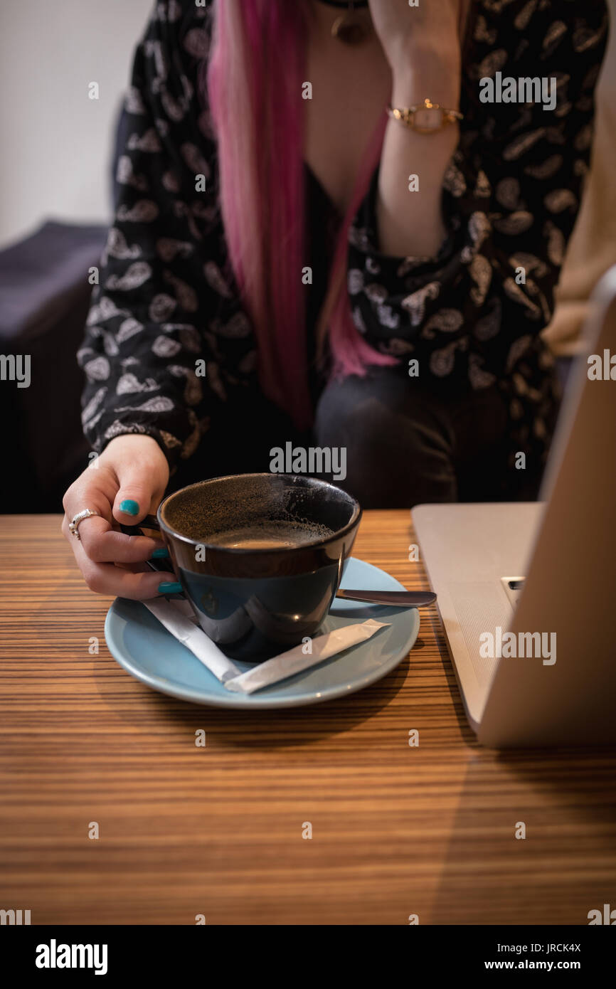 Mid section of attractive woman having coffee in cafe - Stock Image
