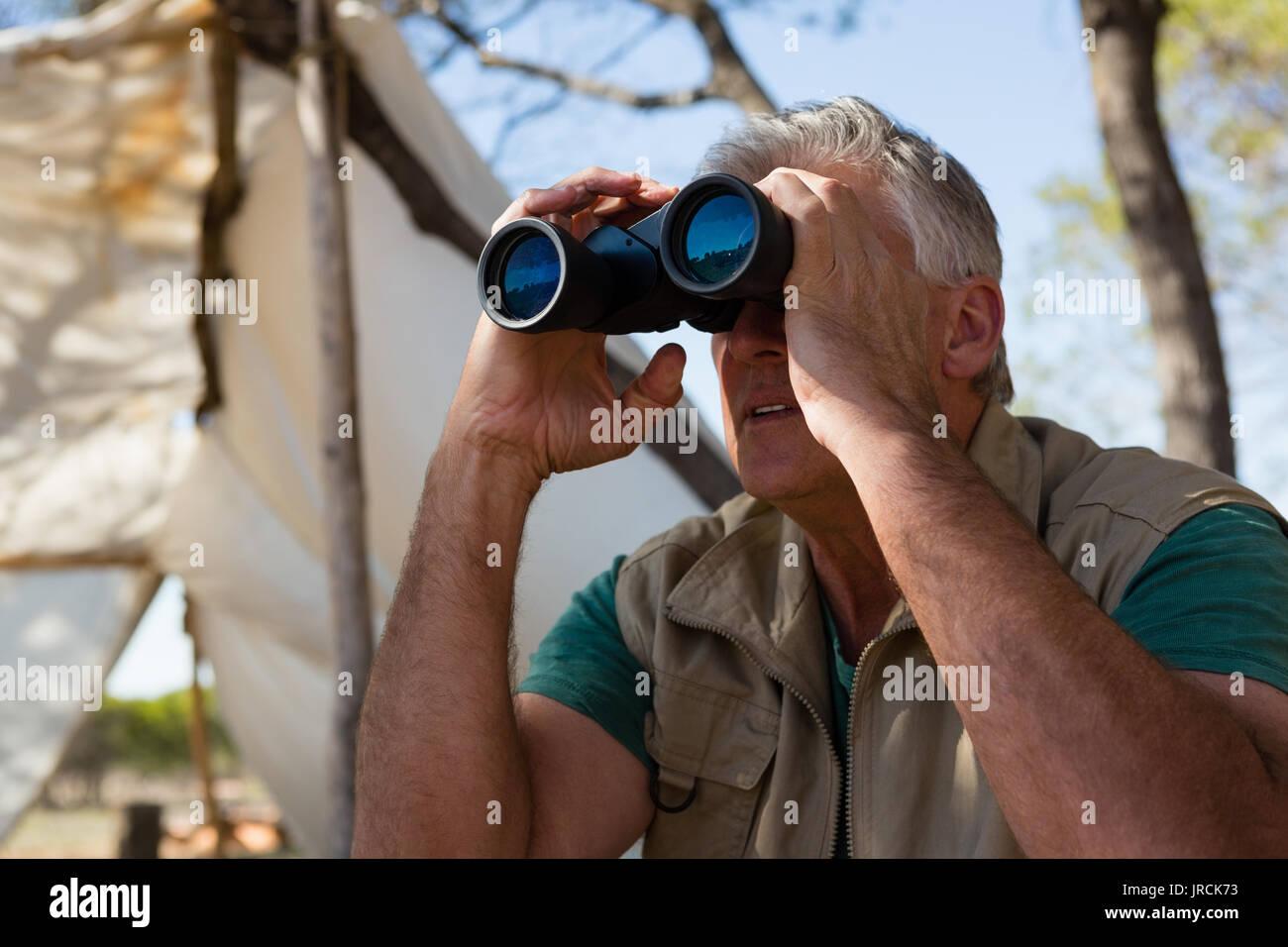 Mature man looking through binocular outside tent - Stock Image