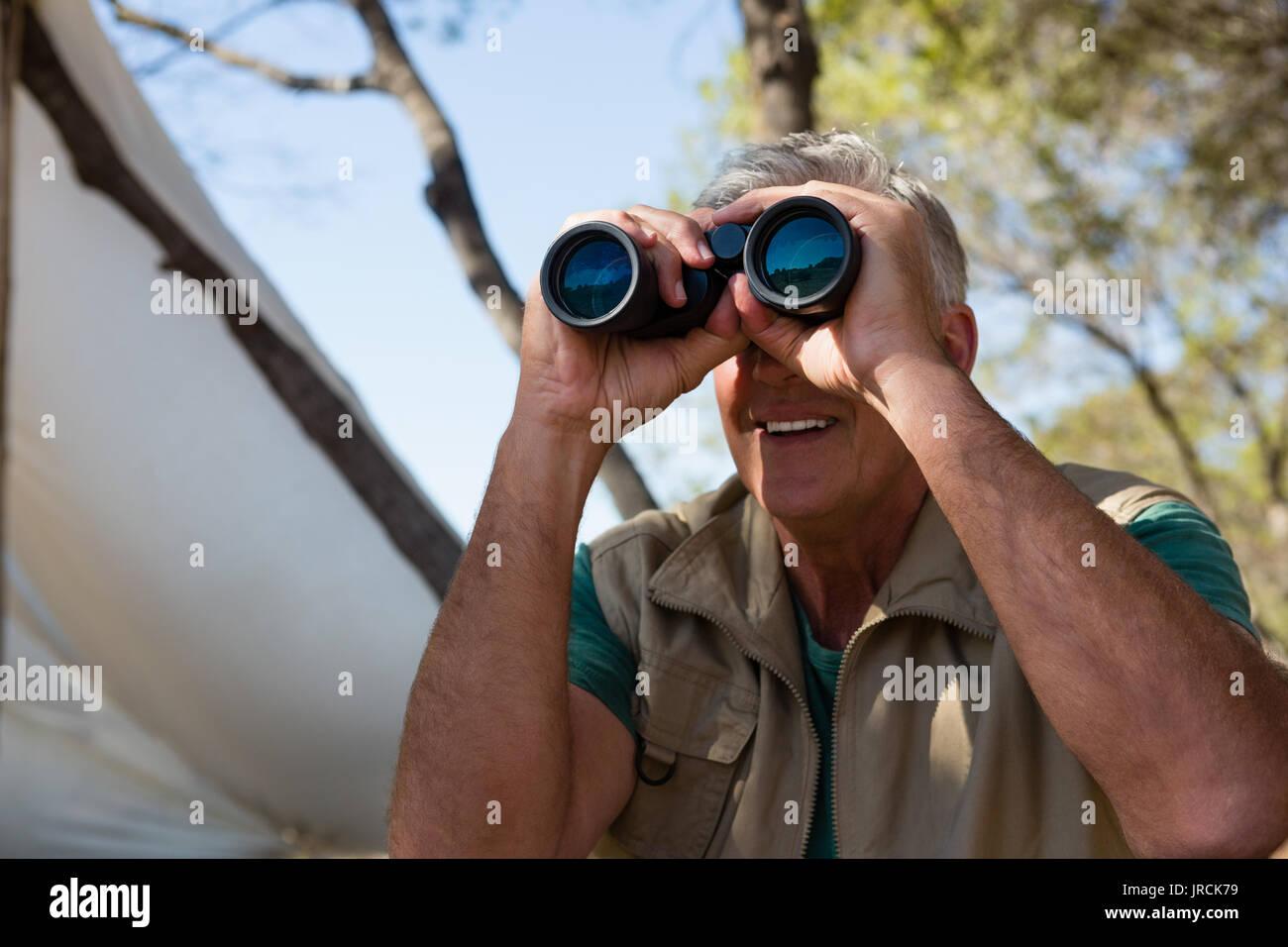 Mature man looking through binocular by tent - Stock Image