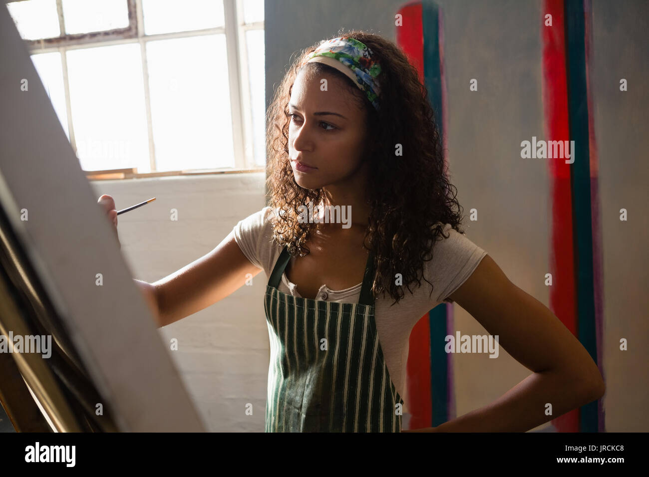 Woman painting on artists canvas in art class - Stock Image