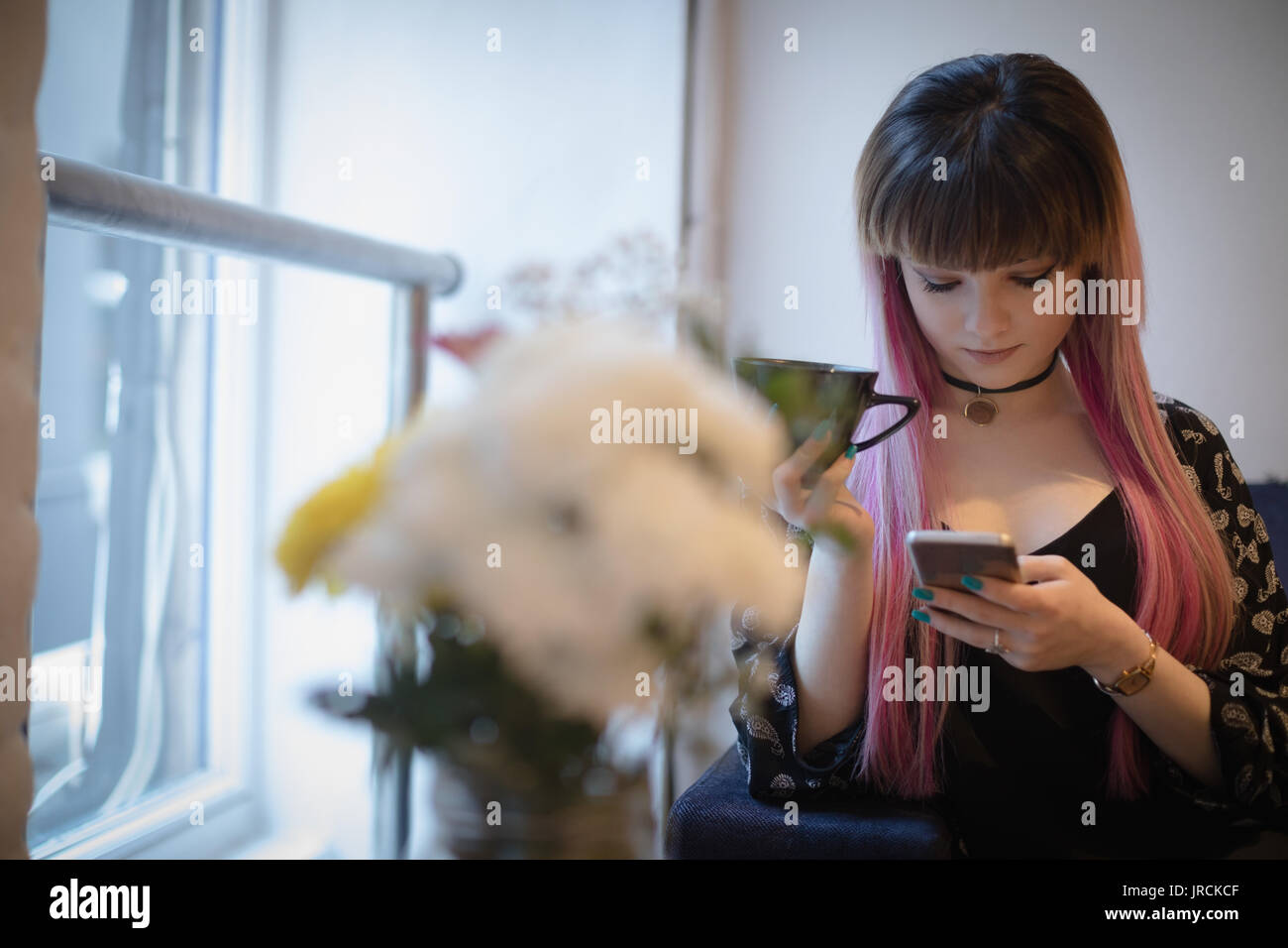 Beautiful woman having coffee while using mobile phone in cafe - Stock Image