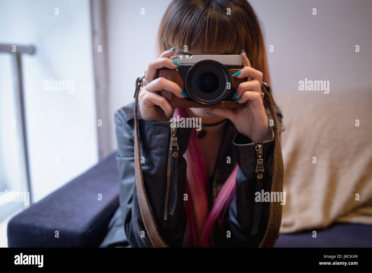 Attractive woman taking photo from digital camera in cafe - Stock Image