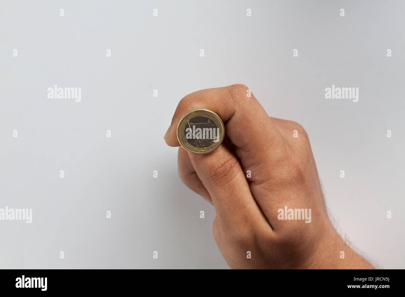 close-up of a hand throwing a euro coin - Stock Image