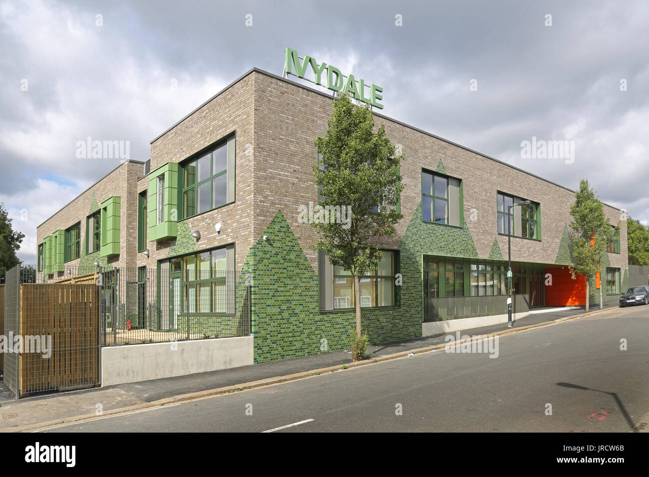 Exterior view of the newly completed Ivydale Primary School in Nunhead, southeast London, UK.Grey brick with large triangles of glazed green bricks. - Stock Image