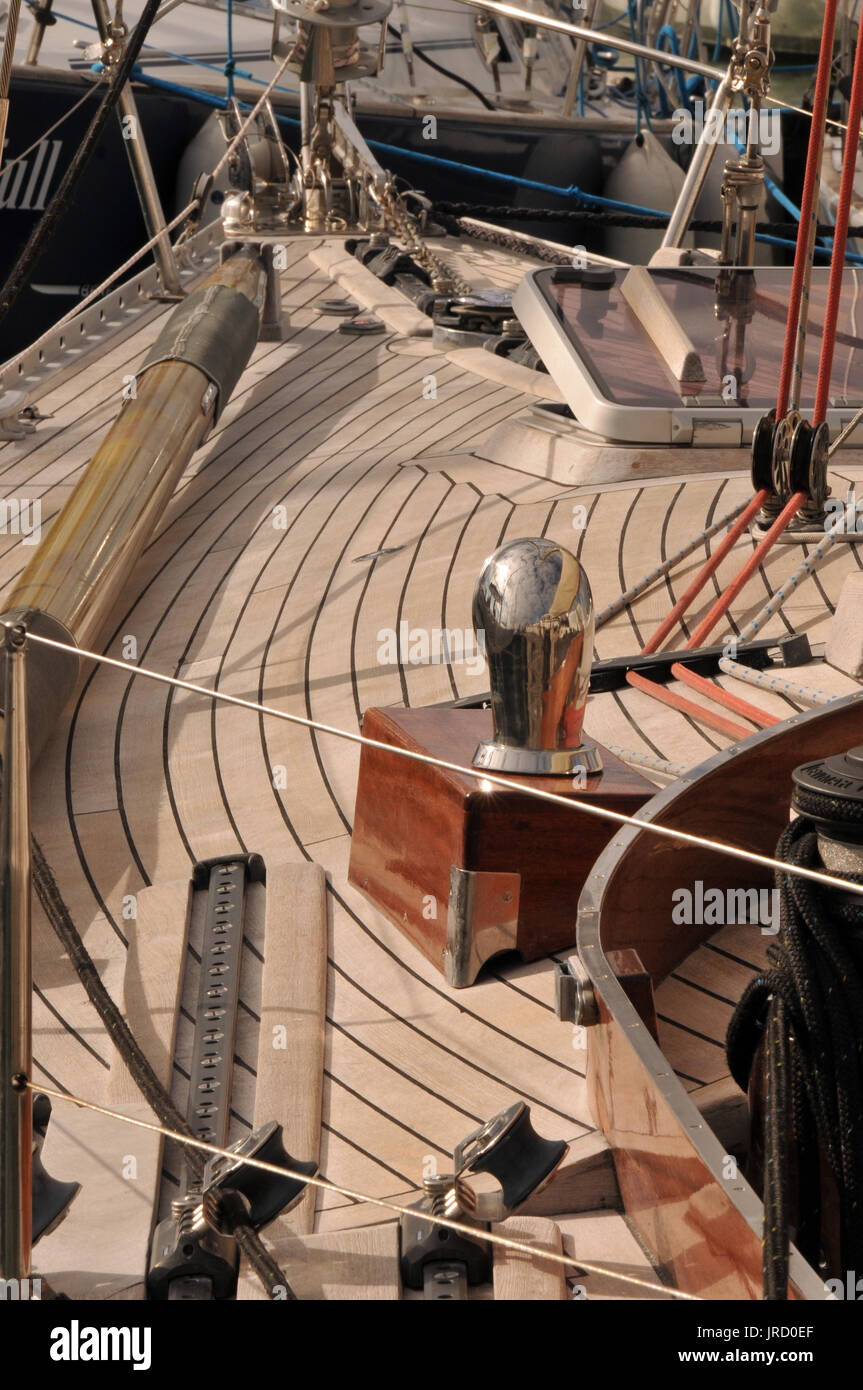 The beautifully laid and caulked wooden deck of a large traditional classic sailing yacht or boat at poles week on the Isle of Wight with brass bits. - Stock Image
