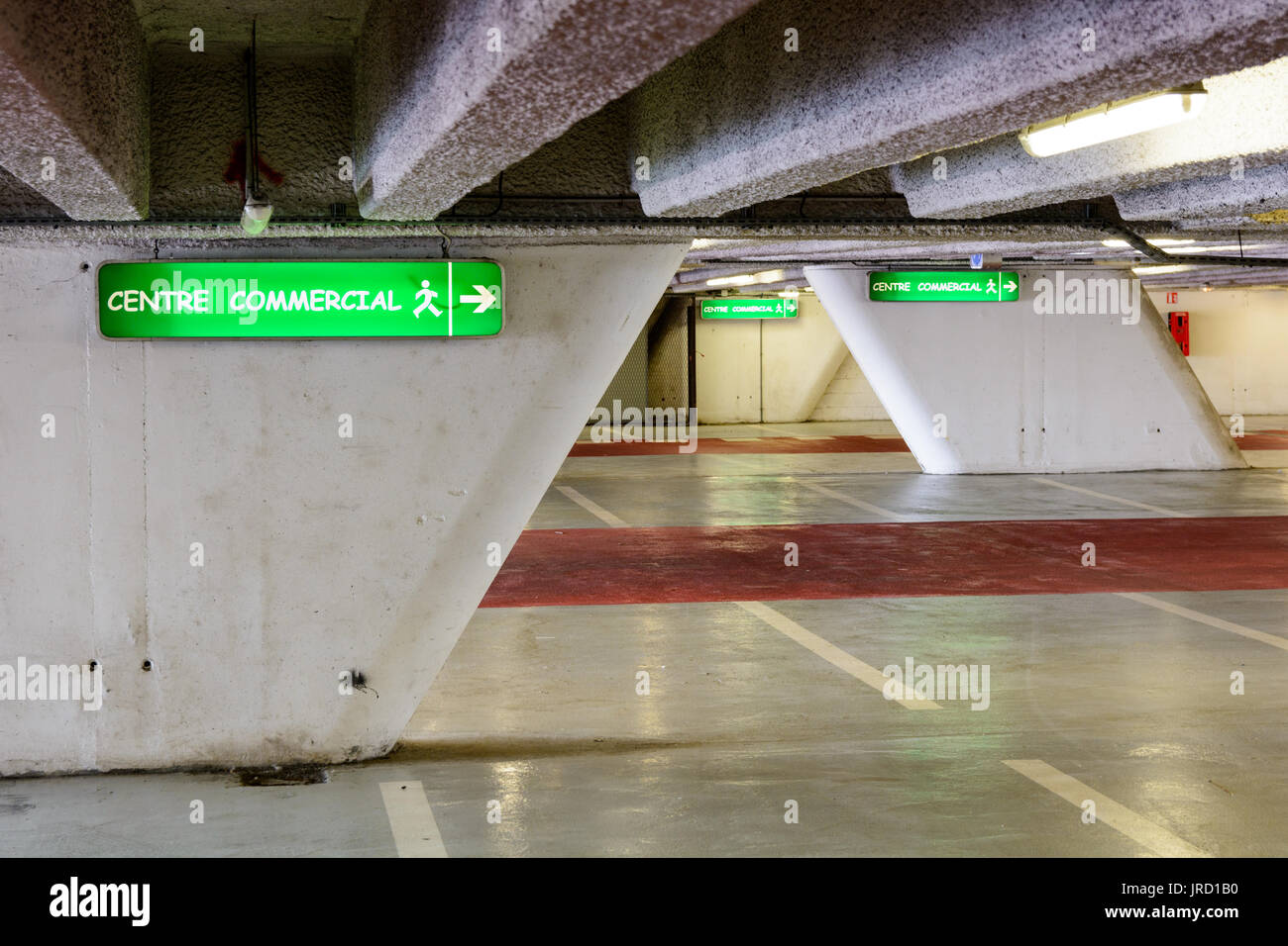 Luminous signs indicating the direction to the commercial center in an old decrepit underground parking lot. - Stock Image