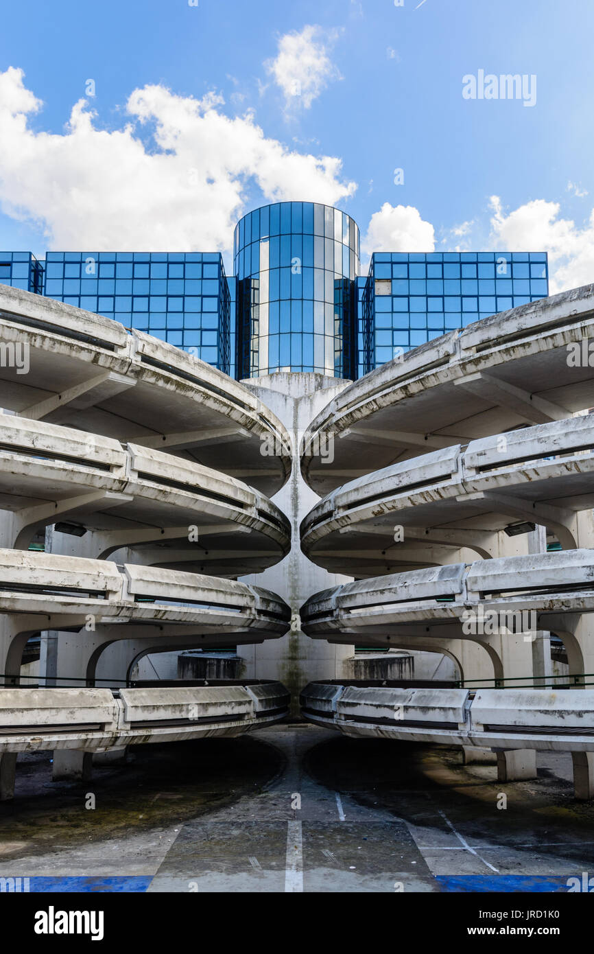 Spiral access ramps of an old decrepit concrete parking lot with a glass office building in the background. - Stock Image
