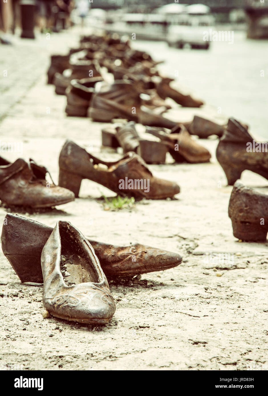 Shoes monument on the Danube bank is a memorial in Budapest, Hungary. Place of reverence. Symbolic object. Retro photo filter. - Stock Image