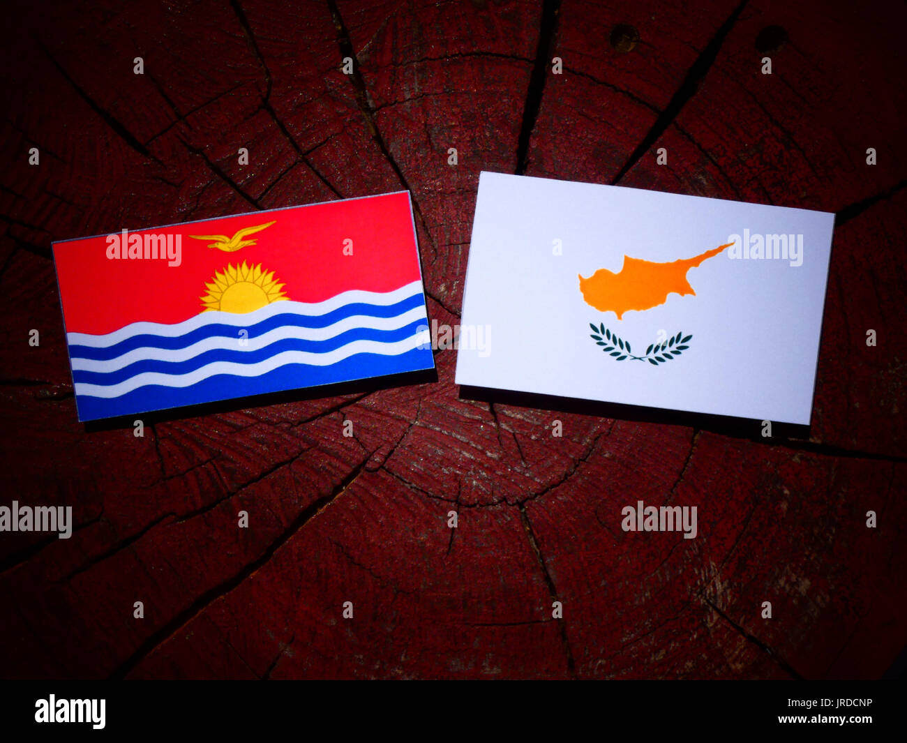 Kiribati flag with Cypriot flag on a tree stump isolated - Stock Image