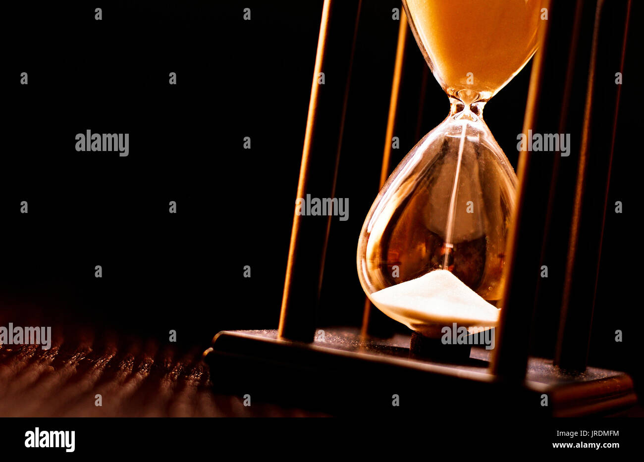 Newly turned hourglass with running sand measuring the passing time to a deadline or expiry of a fixed time period, close up on a dark background - Stock Image