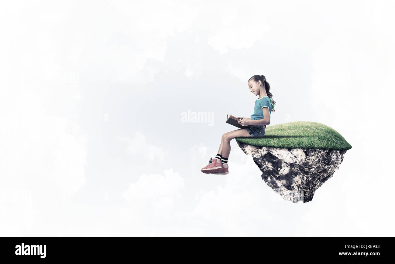 Concept of careless happy childhood with girl reading book - Stock Image