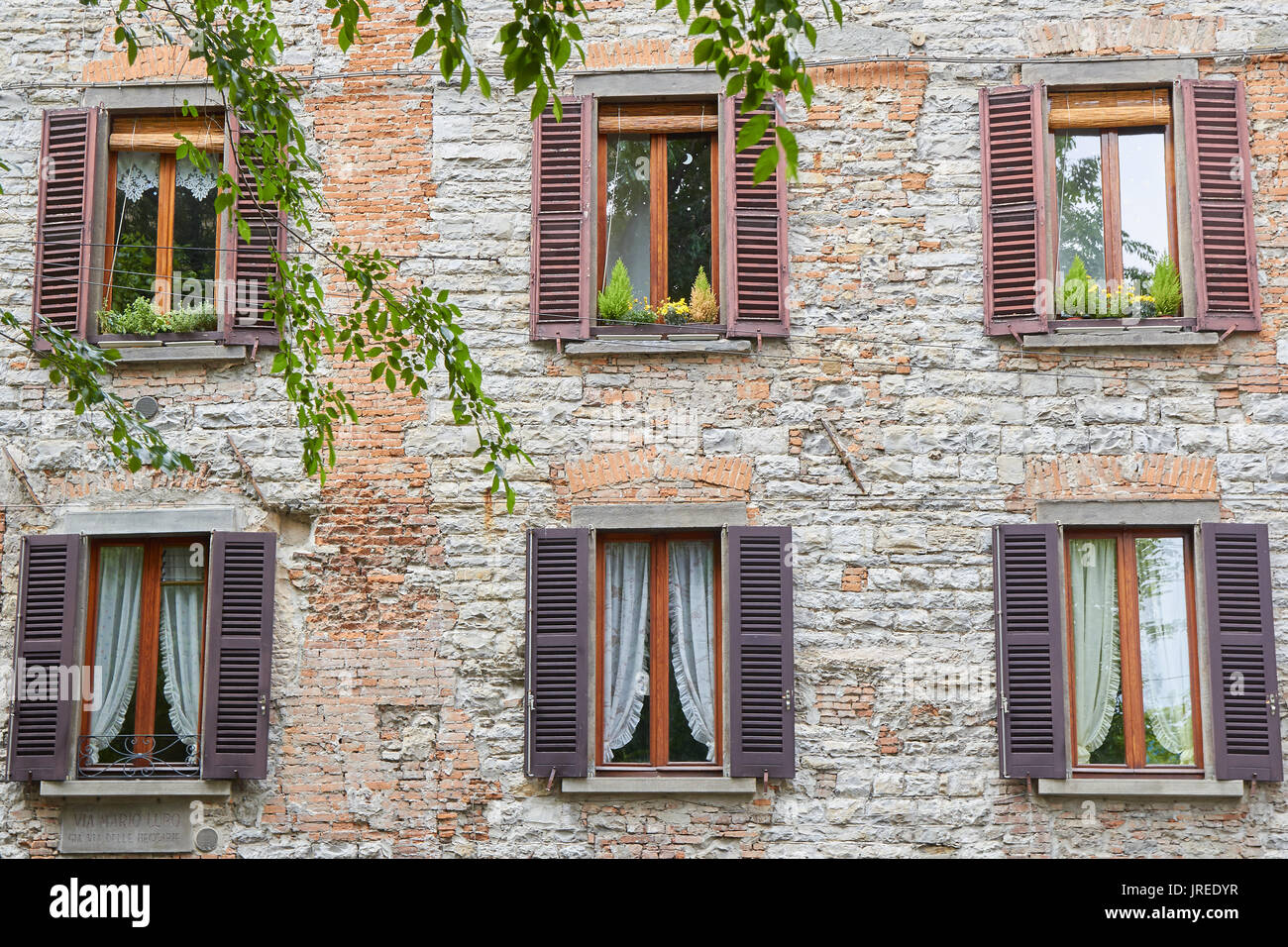 Six wood windows on a brick facade in a street of the town of Bergamo (Italy) - Stock Image
