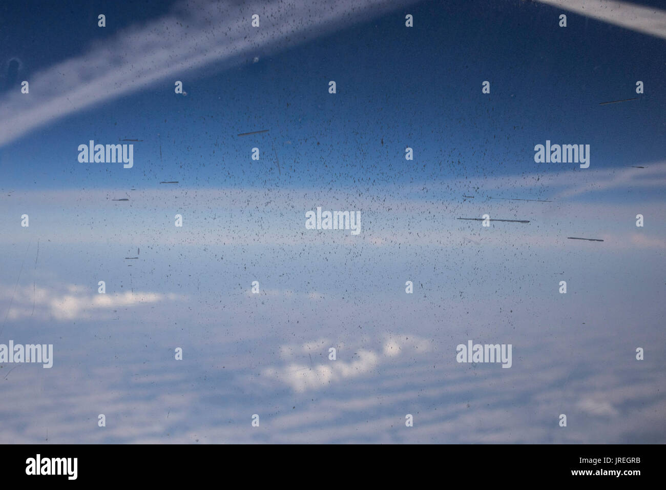 View of sky from dirty aeroplane window. - Stock Image