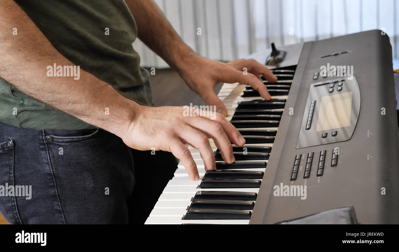 Man playing electric piano or electronic keyboard - Stock Image