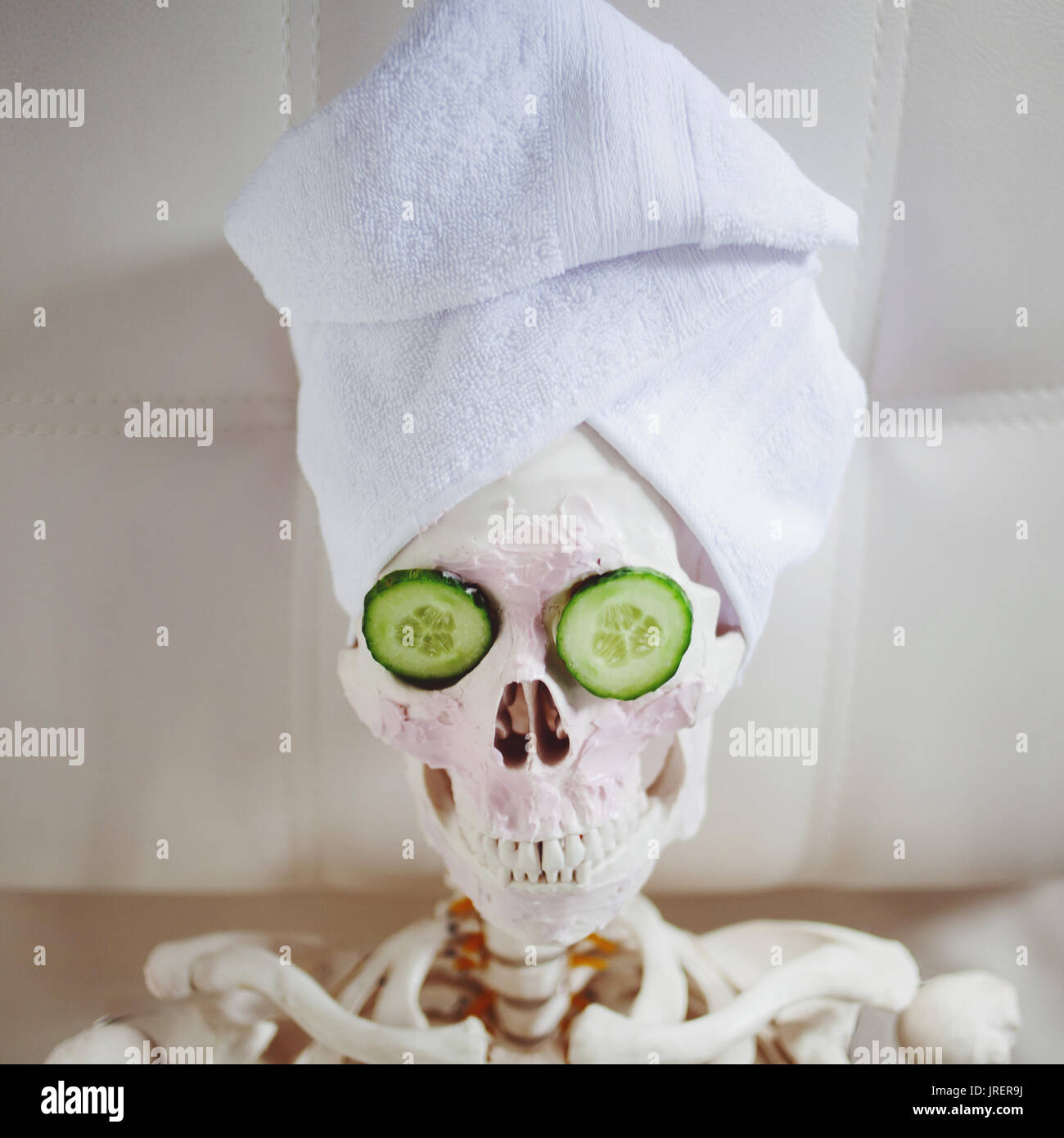 Skeleton in Spa salon with towel on her head and mask on her face, relaxes. An absurd concept, social parody. Take care of beauty and forget about inn - Stock Image
