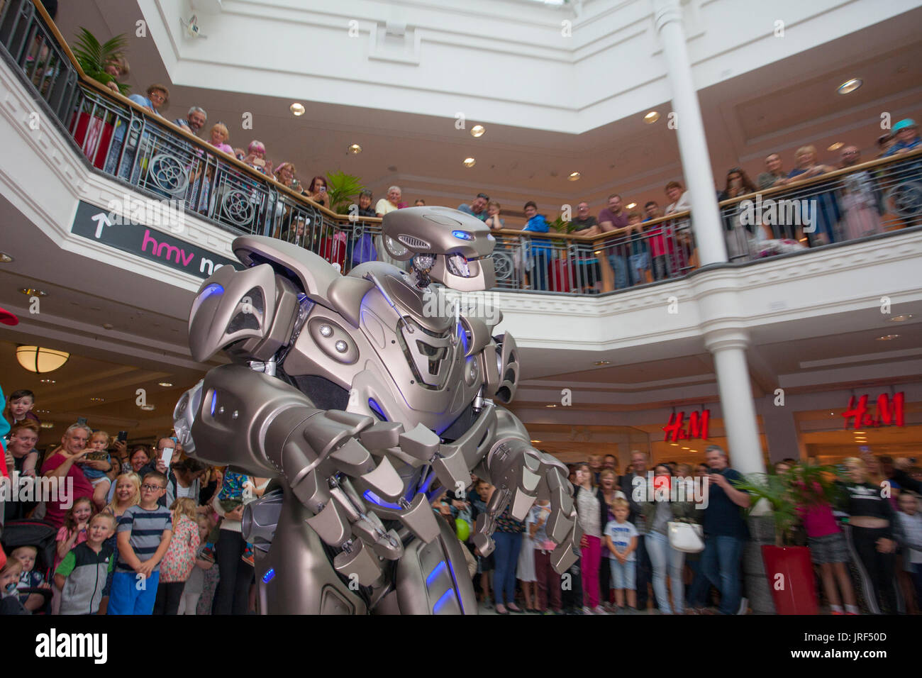 Preston, Lancashire, UK. Titan the robot, wearing an exoskeleton suit, wows the crowds at St George's Centre. Titan is the stage name of a partially-mechanised costume created by Cyberstein Robots Ltd. The robot costume is approximately 2.4 metres (7.9 ft) tall and 60 kg and increases to 350 kg including the cart it rides on and onboard equipment. The face resembles a skull, and some have even compared it to a Transformer. It was designed by Nik Fielding, who runs Cyberstein from Newquay, Cornwall, England. - Stock Image