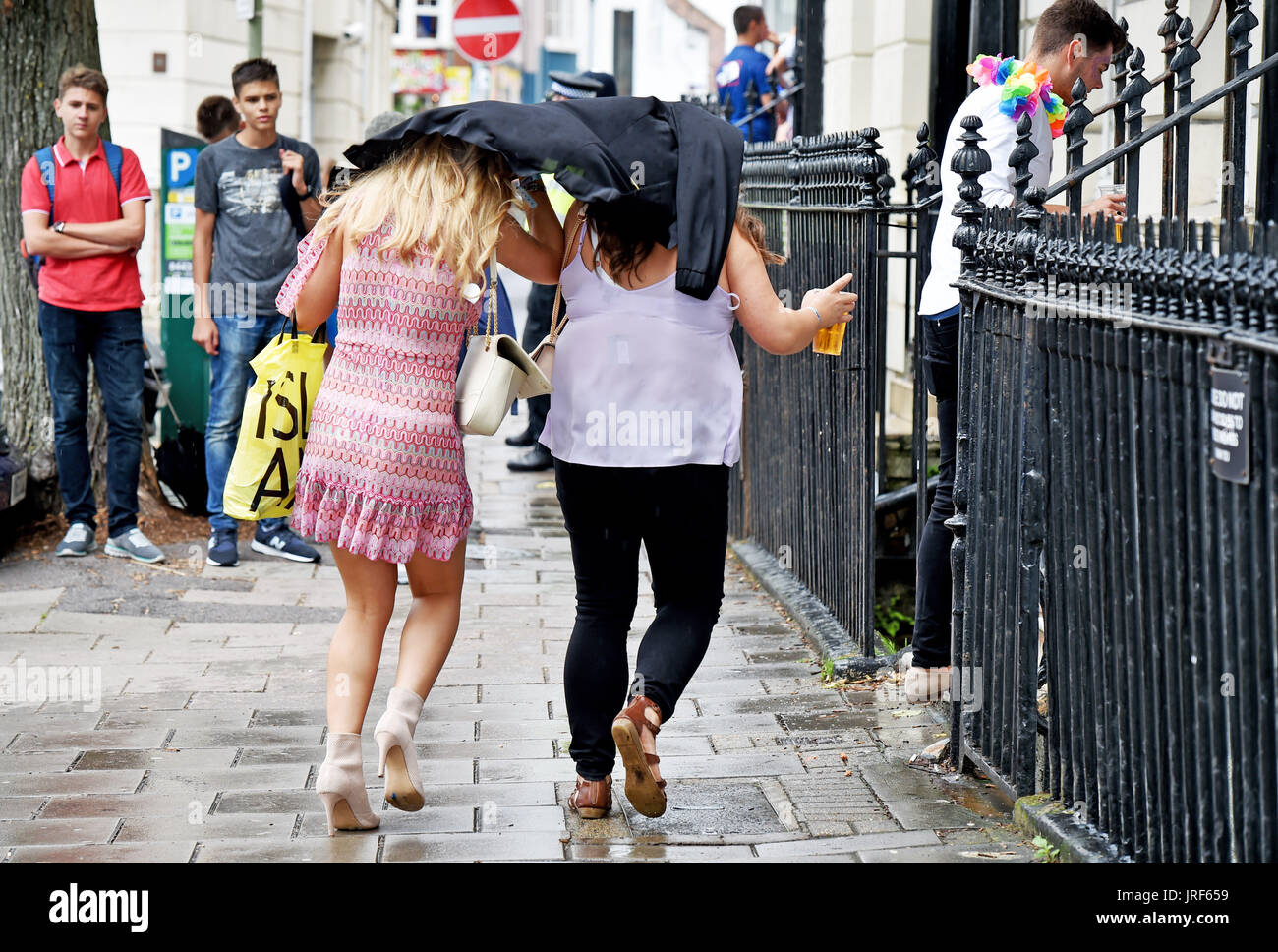 Brighton, UK. 5th Aug, 2017. Party goers at Brighton Pride rush for cover as heavy rain showers sweep across the south east of Britain this afternoon Credit: Simon Dack/Alamy Live News - Stock Image