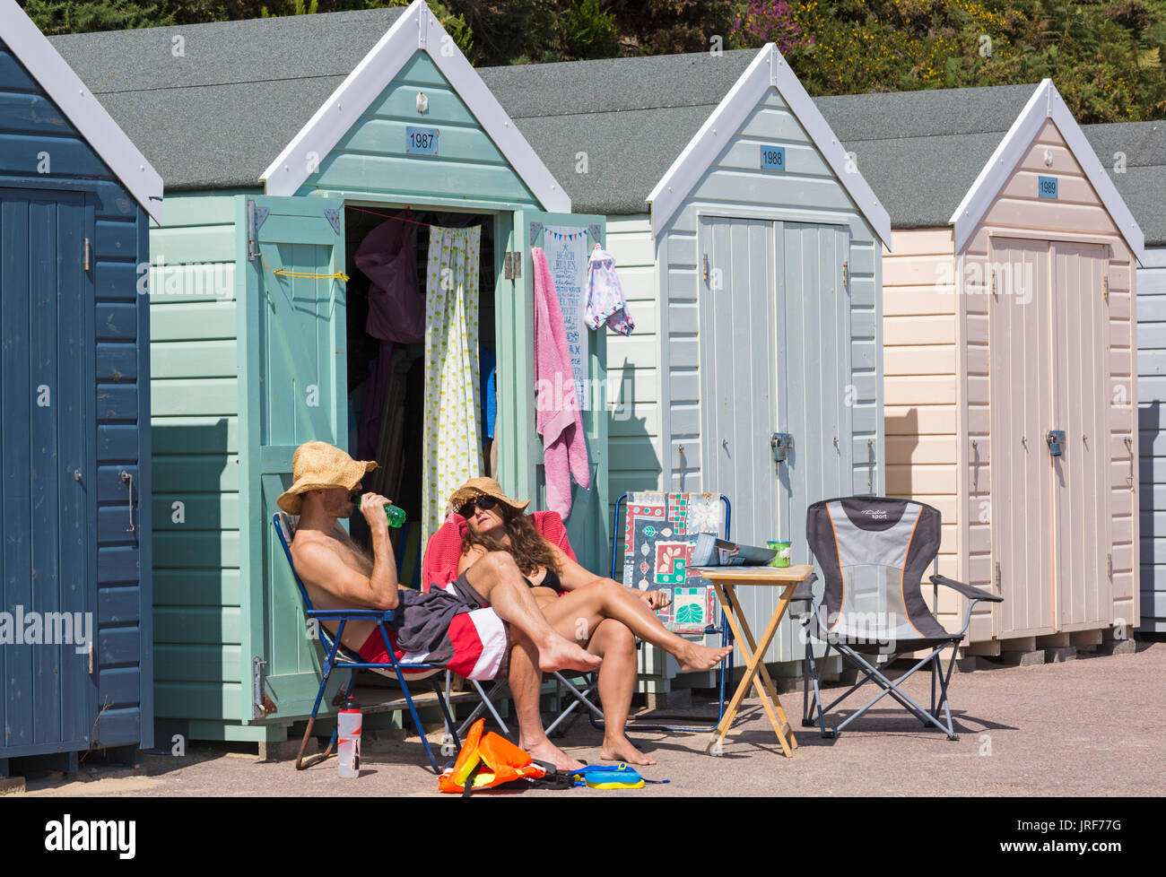 Bournemouth, Dorset, UK. 5th Aug, 2017. UK weather: nice warm sunny afternoon, as visitors head to the seaside to make the most of the sunshine at Alum Chine beach. Couple relaxing outside beach huts enjoying the sunshine. Credit: Carolyn Jenkins/Alamy Live News Stock Photo