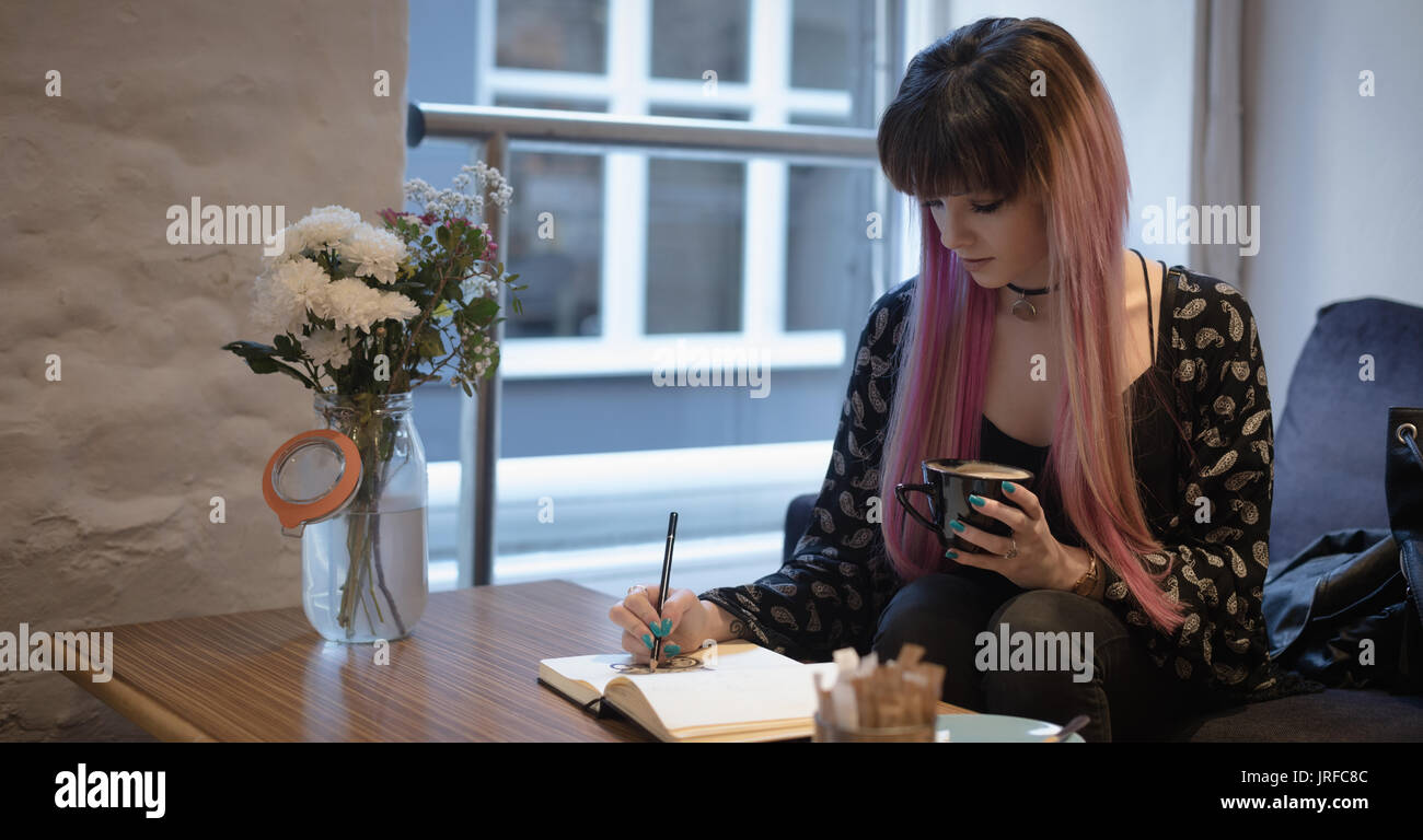 Beautiful woman making design in book while having coffee in cafe - Stock Image