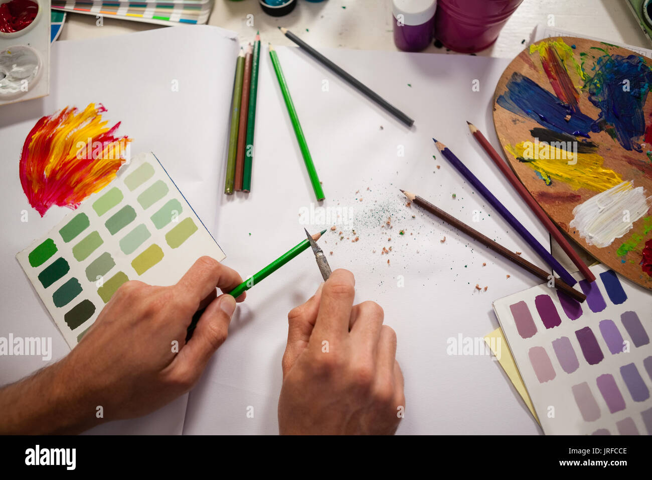 Man sharpening colored pencil in drawing class - Stock Image