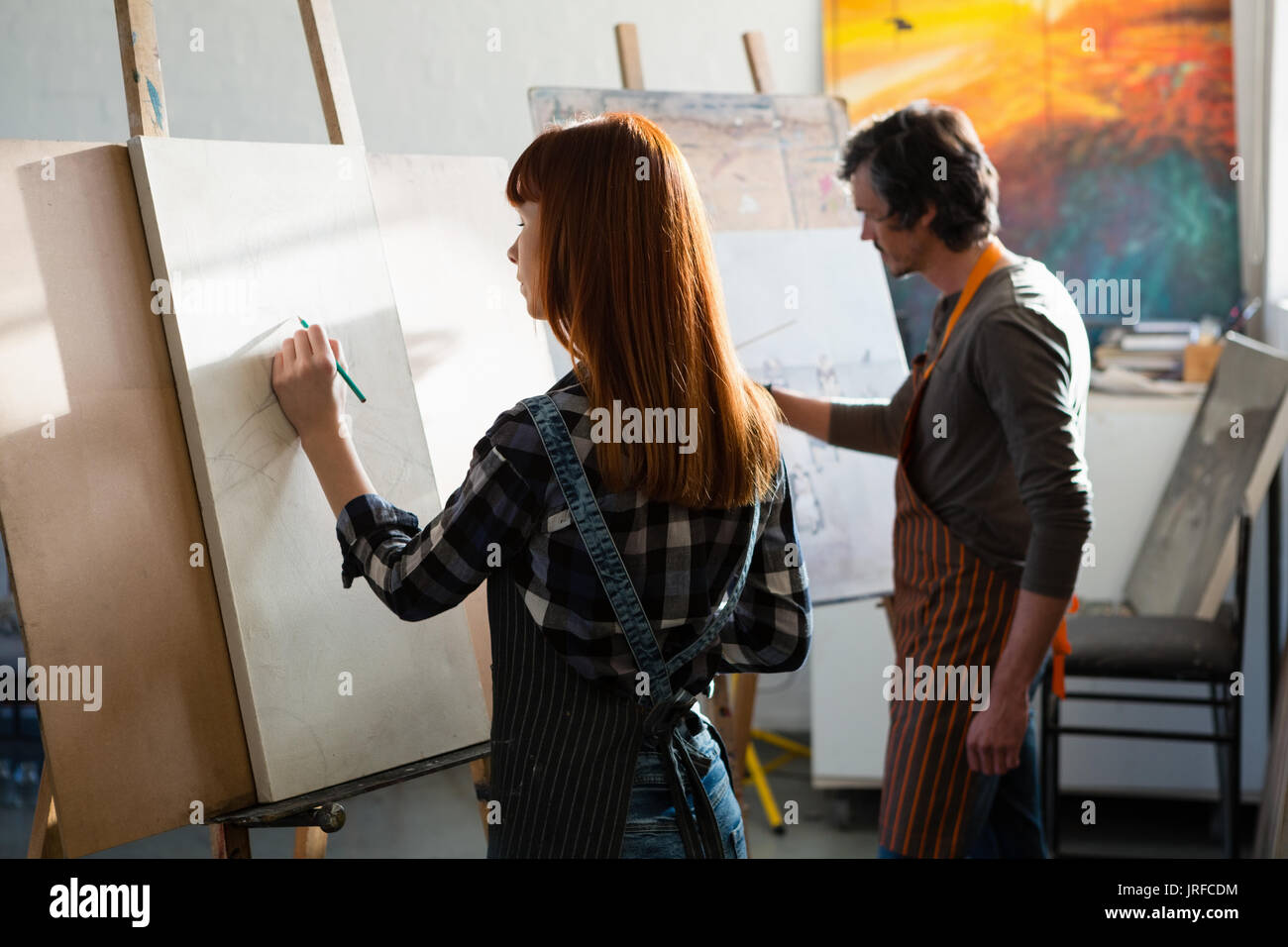 Man and woman drawing on artists canvas in art class - Stock Image