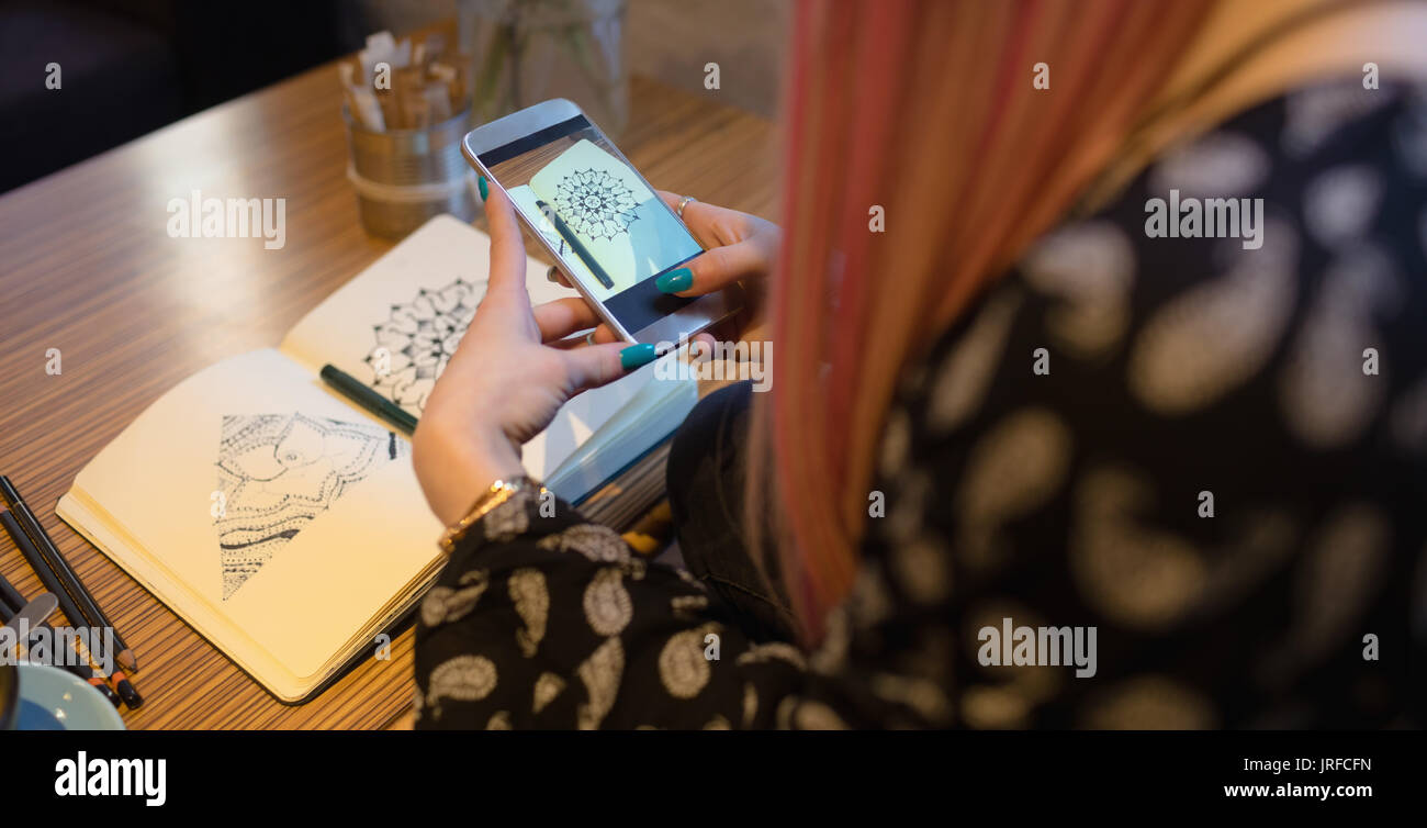 Woman clicking picture from mobile phone in cafe - Stock Image