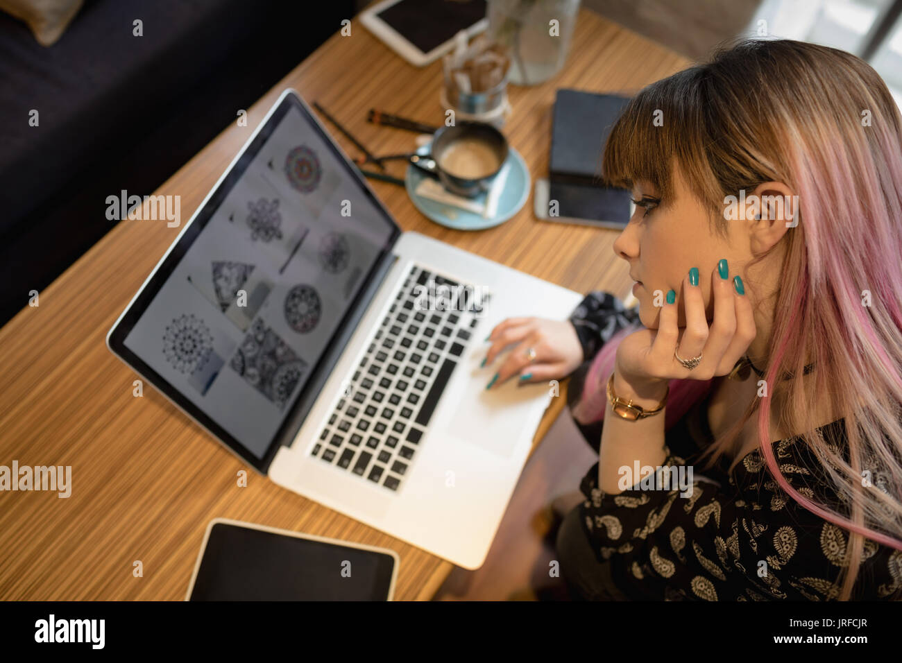 Beautiful woman using laptop at table in cafe - Stock Image