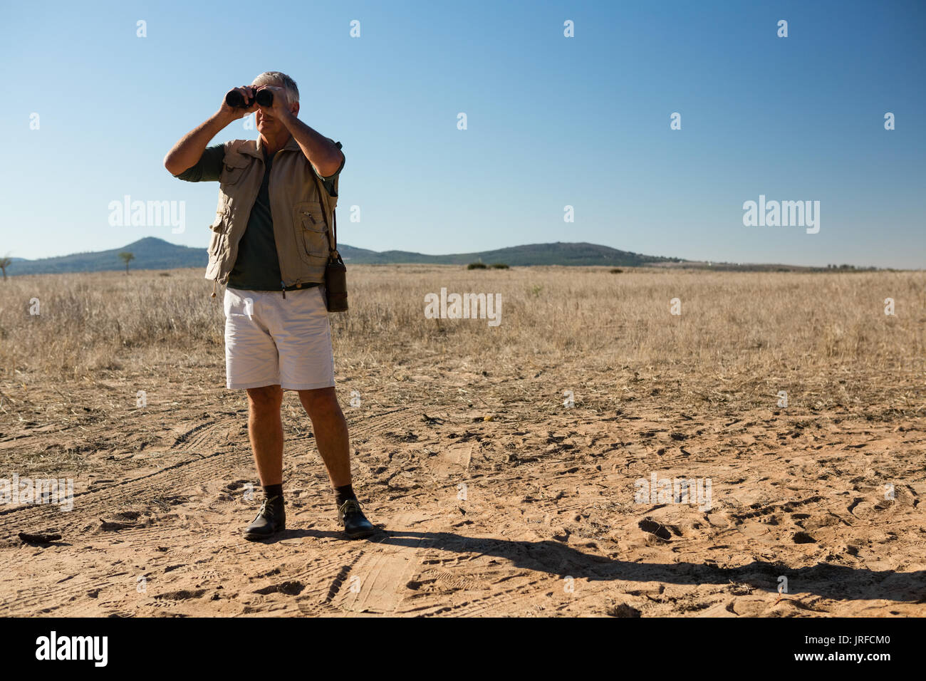 Man looking through binocular while standing on landscape during sunny day - Stock Image