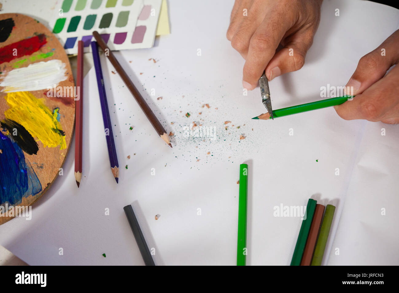 Close-up of man sharpening colored pencil in drawing class - Stock Image