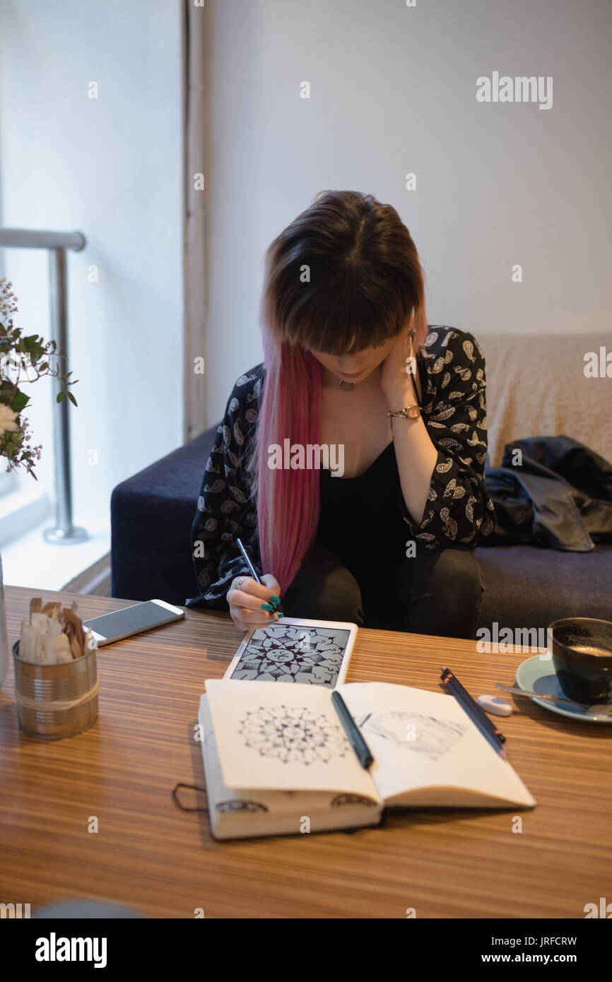Beautiful woman using digital tablet in cafe - Stock Image