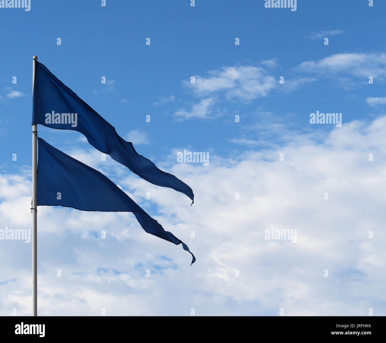 Blue triangular banner flags flying atop flagpole against sky - Stock Image