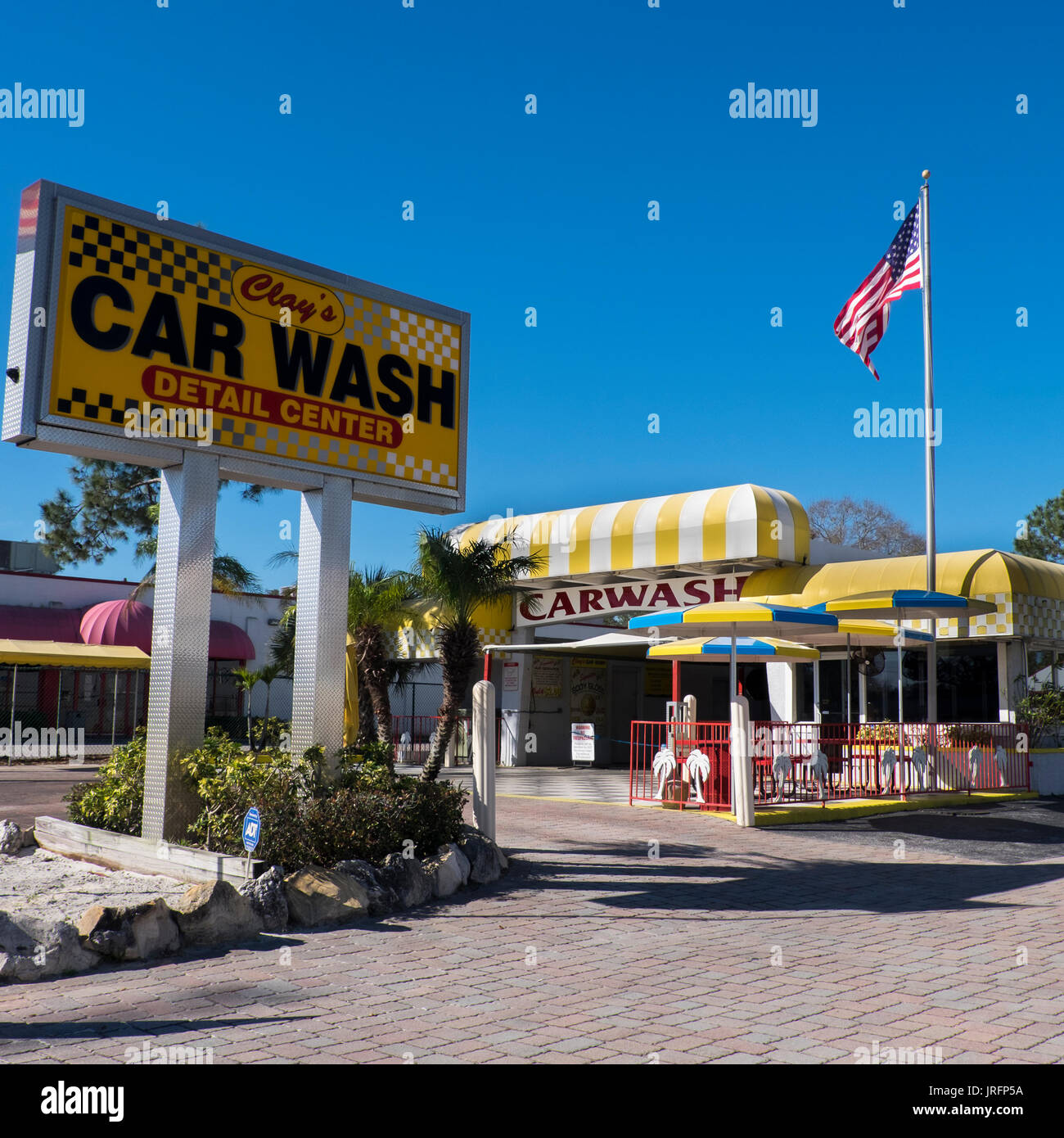 Classic Americana...a traditional 1950's car wash with American flag along a highway in Florida - Stock Image