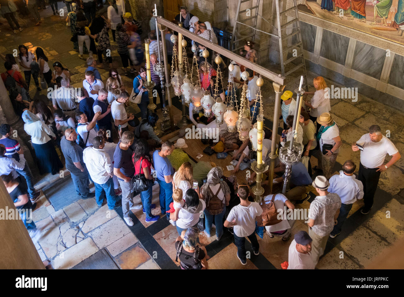A crowd of penitents gathers around the Stone of Annointing in the Church of the Holy Sepulchre in the Old City of Jerusalem - Stock Image