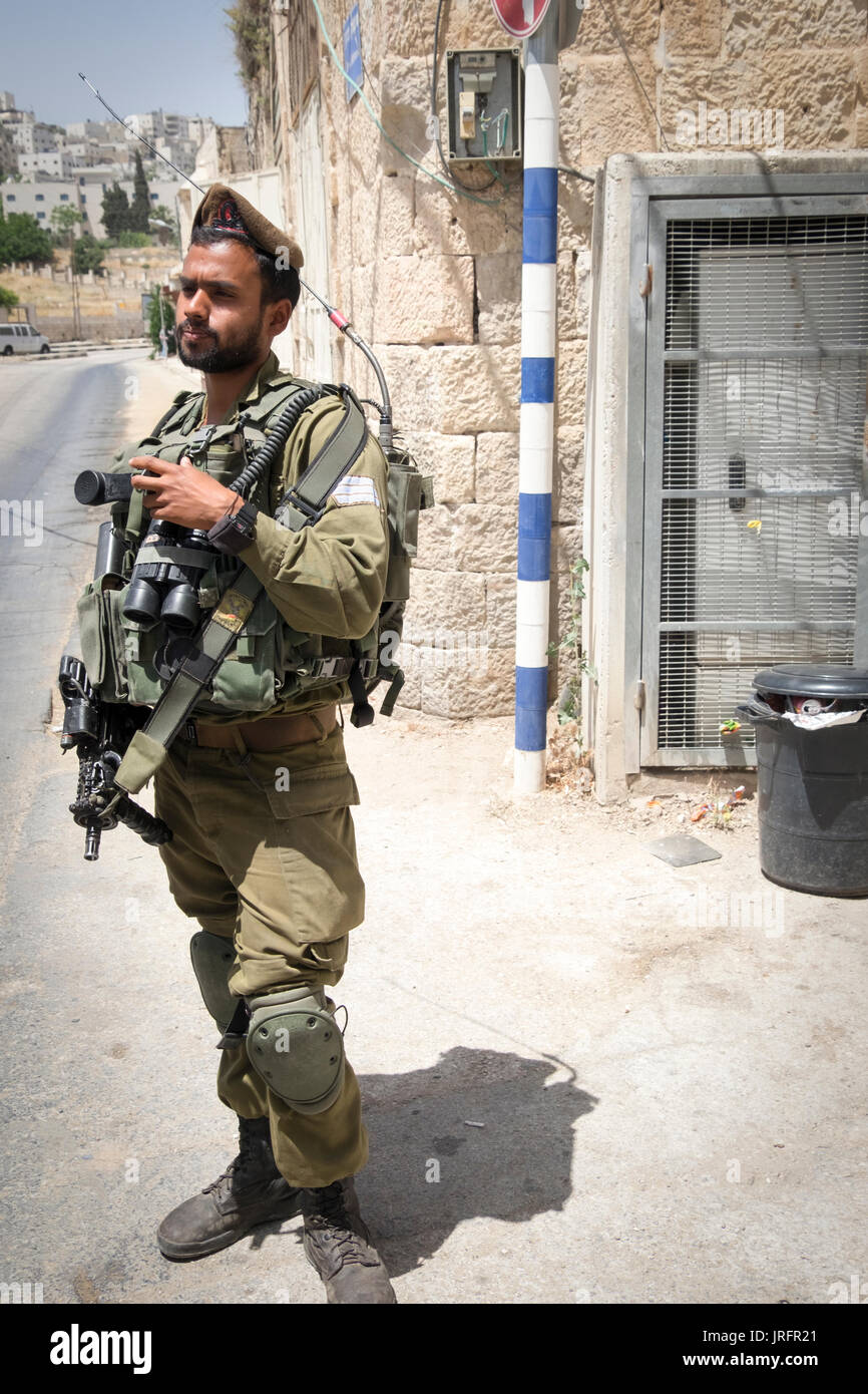 Israeli soldier guarding a former bustiling Hebron market street now closed to Palestinians due to a land grab of 850 Israeli settlers nearby - Stock Image