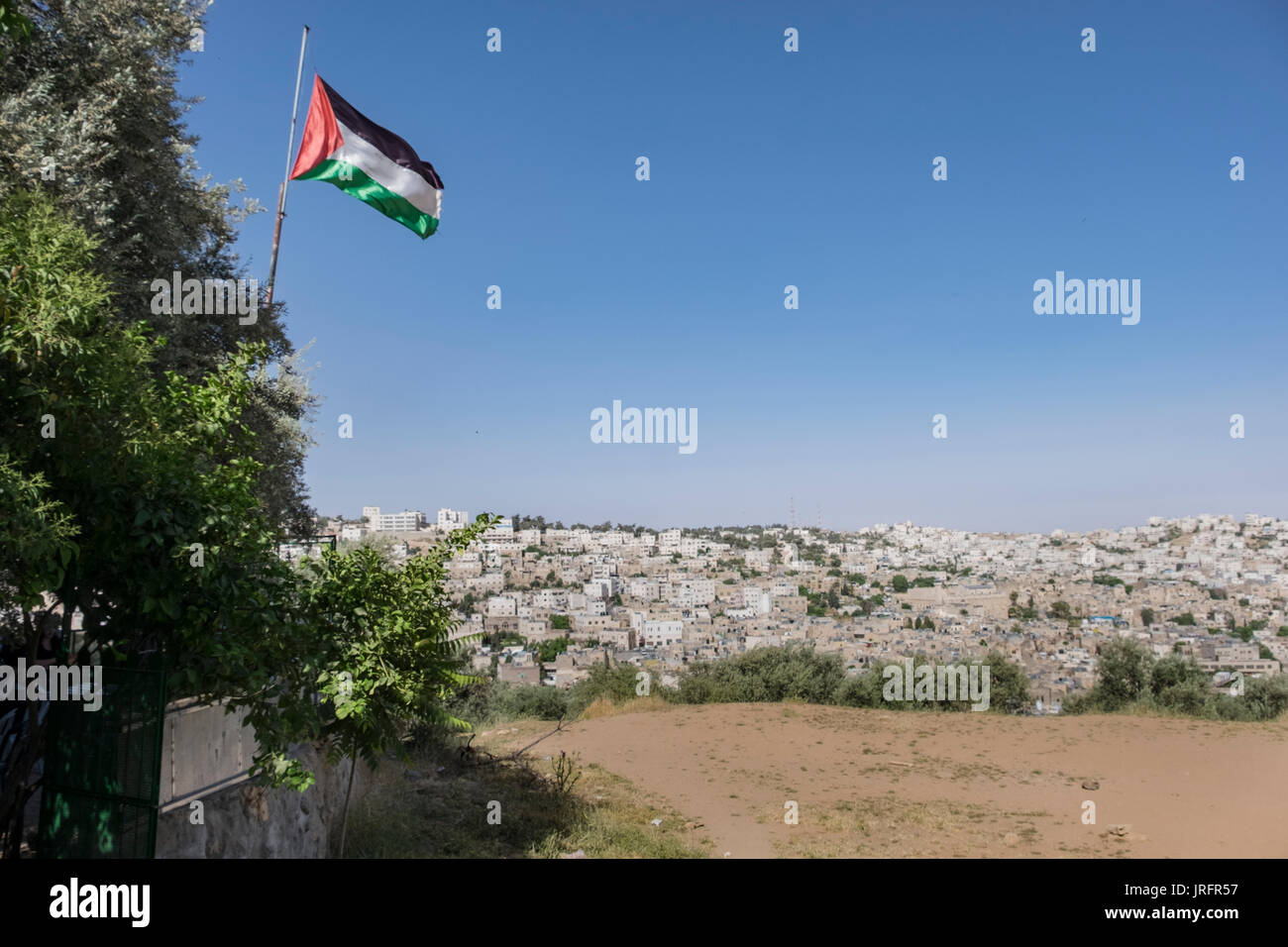 A view of the center of the conflicted city of Hebron as seen from a Palestinian neighborhood overlooking it with a Palestinian flag flying defiantly - Stock Image