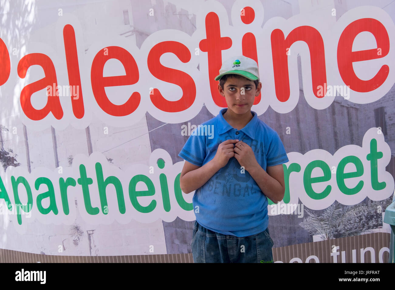 Young Palestinian boy standing in front of a sign protesting the closure of a central street in Hebron, West Bank, Occupied Territories - Stock Image