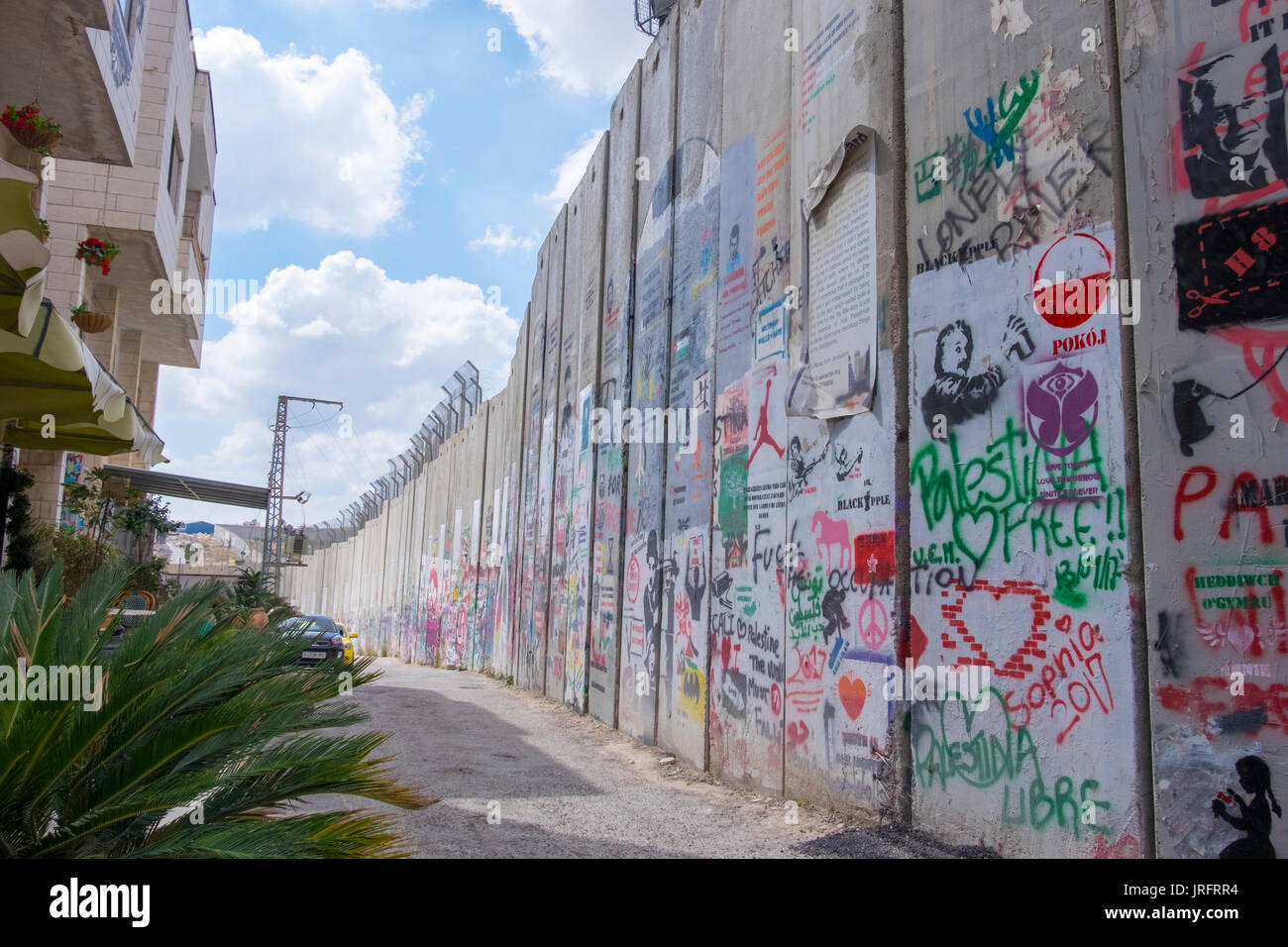 The grafitti filled wall separating Palestine from Israel as it divides the city of Bethlehem in the Occupied Territories of the West Bank - Stock Image