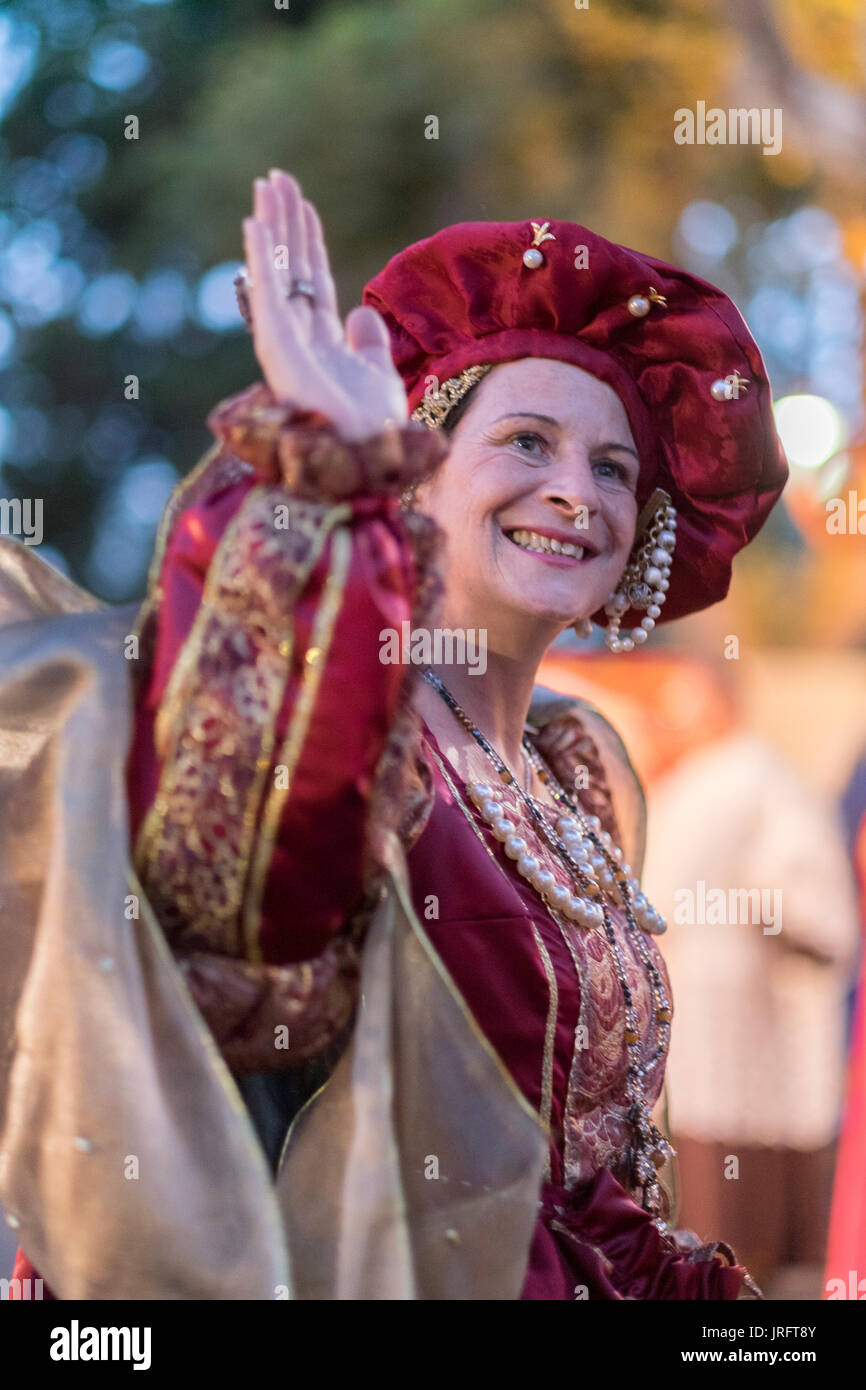 The Queen of a Renaissance Festival in southern France waves to her admirers while dressed in an elaborate costume of the era including jewels & gown. - Stock Image