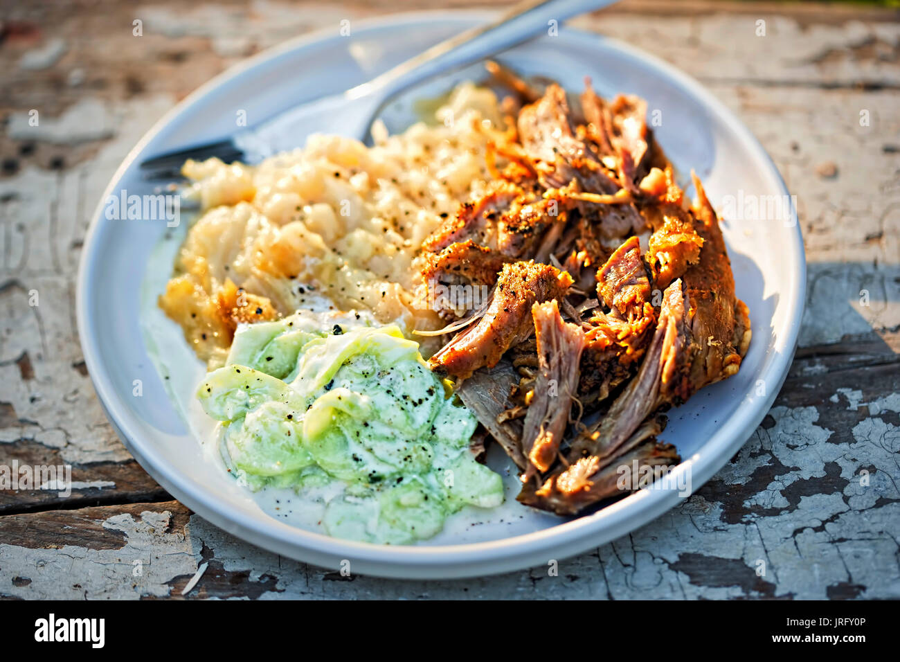 Pulled, seasoned pork, with mashed fried potatoes and cucumber and sour cream salad - Stock Image
