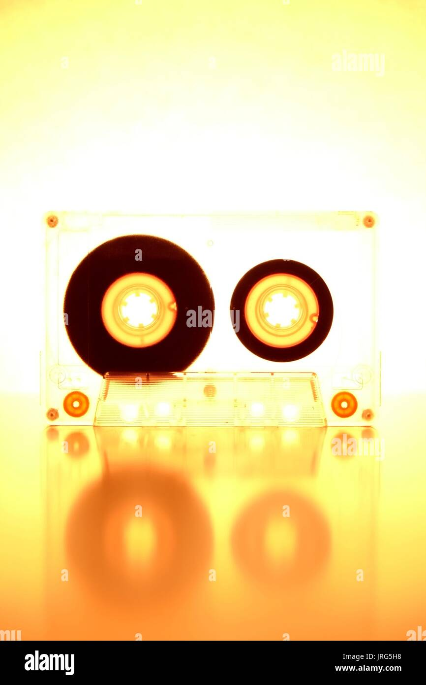Audio cassette tape being backlit on a white background - Stock Image