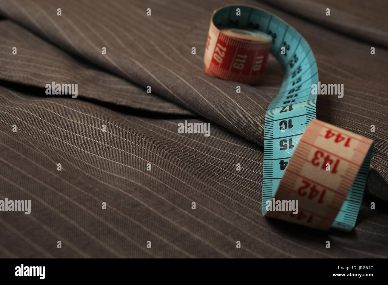 Metric tape on top of a classic gray stripped suit coat - Stock Image