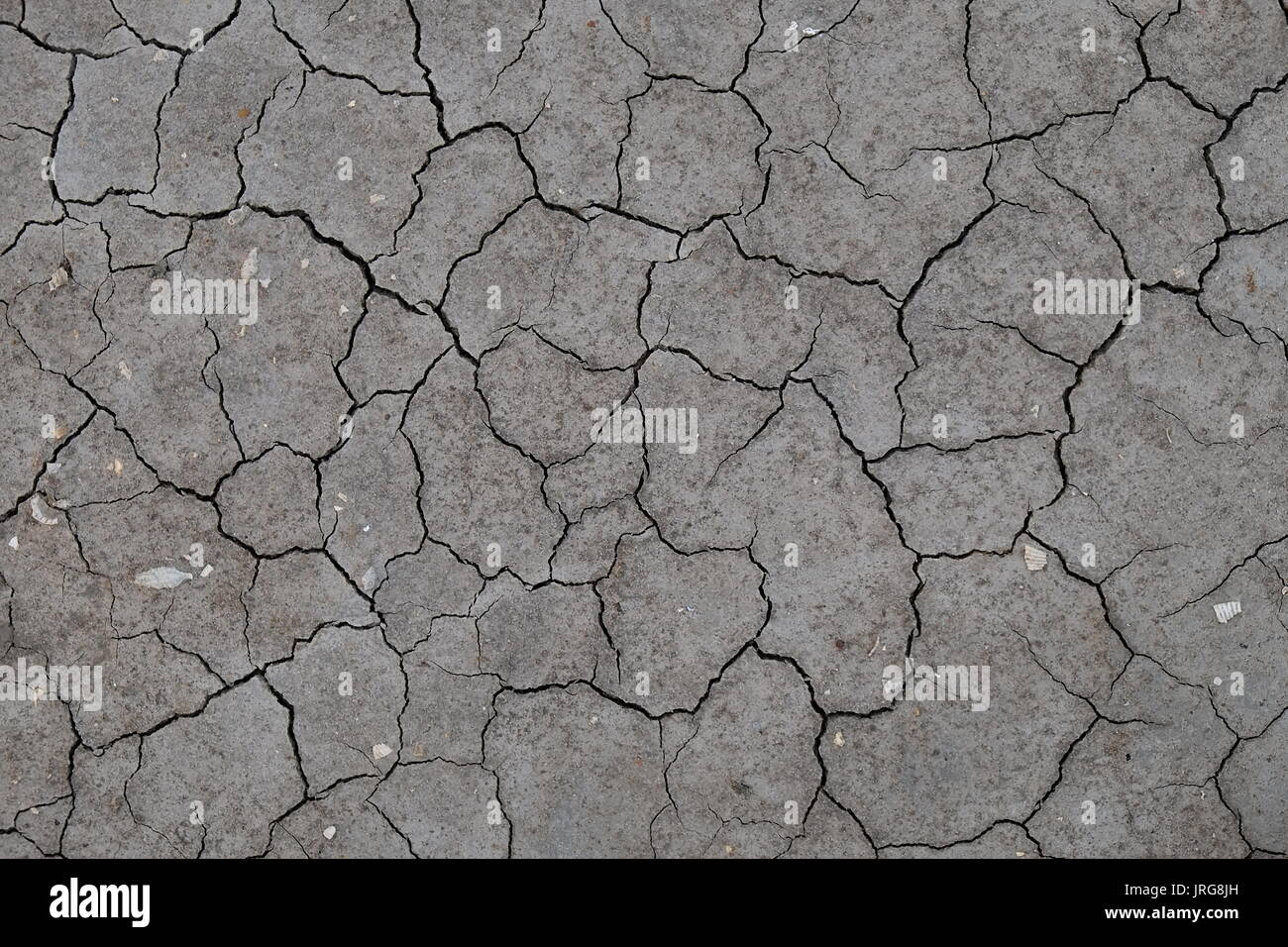 Cracked soil from a dried river bed. Weather and climate change Stock Photo