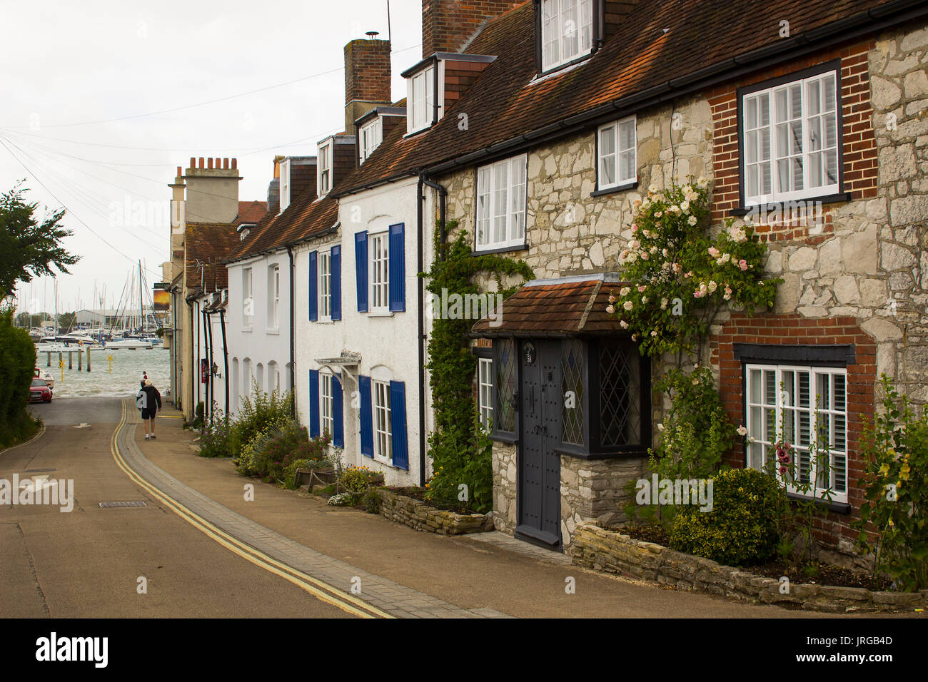 A lone elderly male walks down a street of picturesque terraced houses toward the marina in the village of Warsash Stock Photo