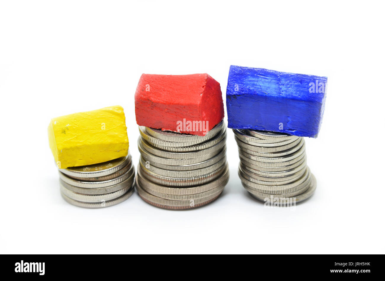 Coins stacked up in piles with color house. Saving for home concept Stock Photo