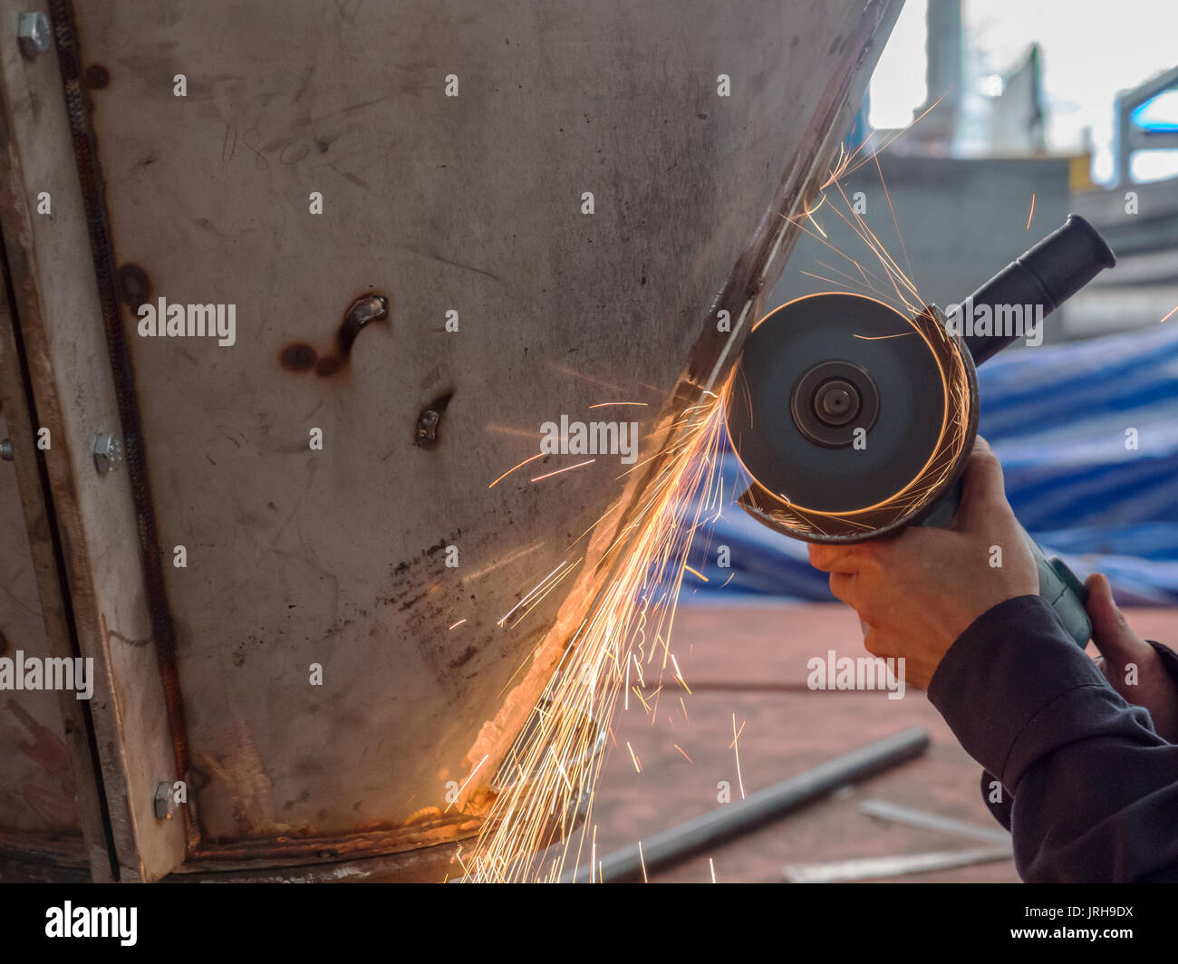 Angle grinder in use at a mechanical workshop. - Stock Image