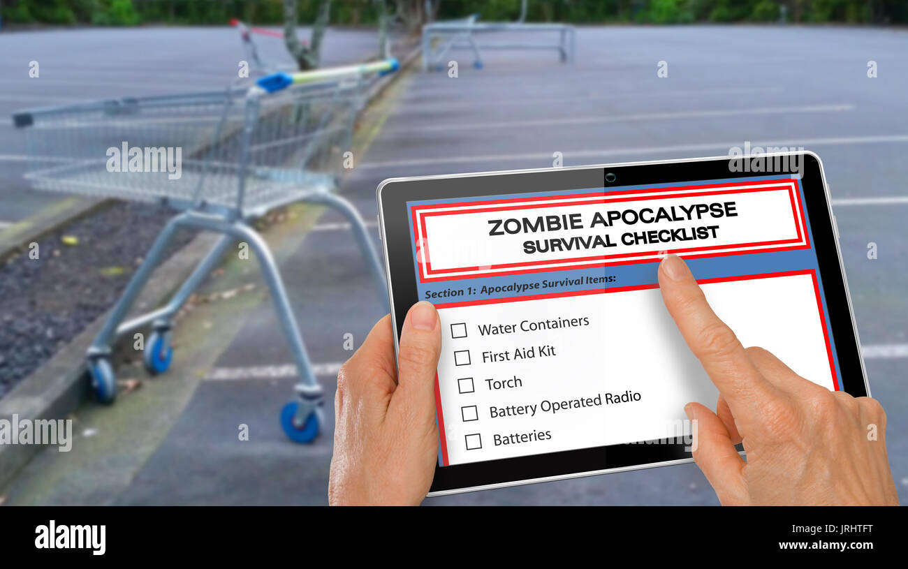 Hand completing Zombie Apocalypse survival checklist on computer tablet - Stock Image