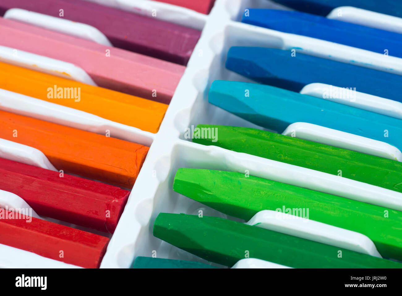 multicolored crayons in plastic box selective focus - Stock Image