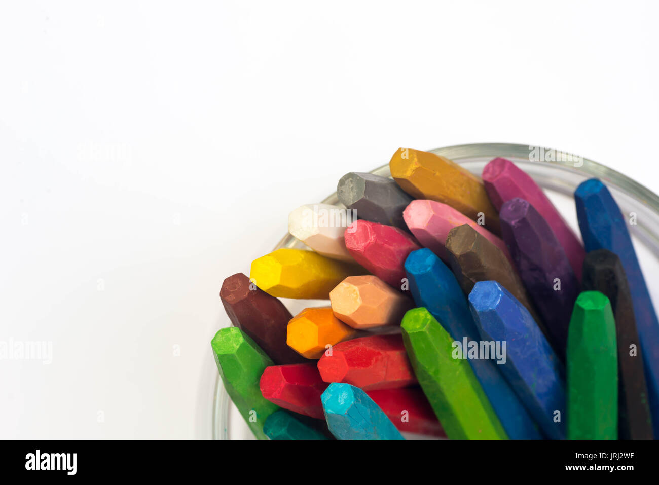multicolored crayons in cup on white paper - Stock Image